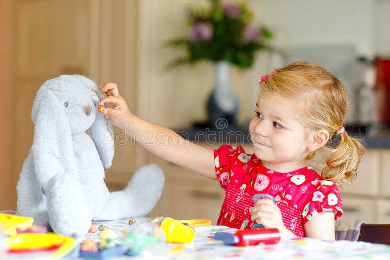 Adorable cute little toddler girl with colorful clay. Healthy baby playing and creating toys from play dough. Small stock images