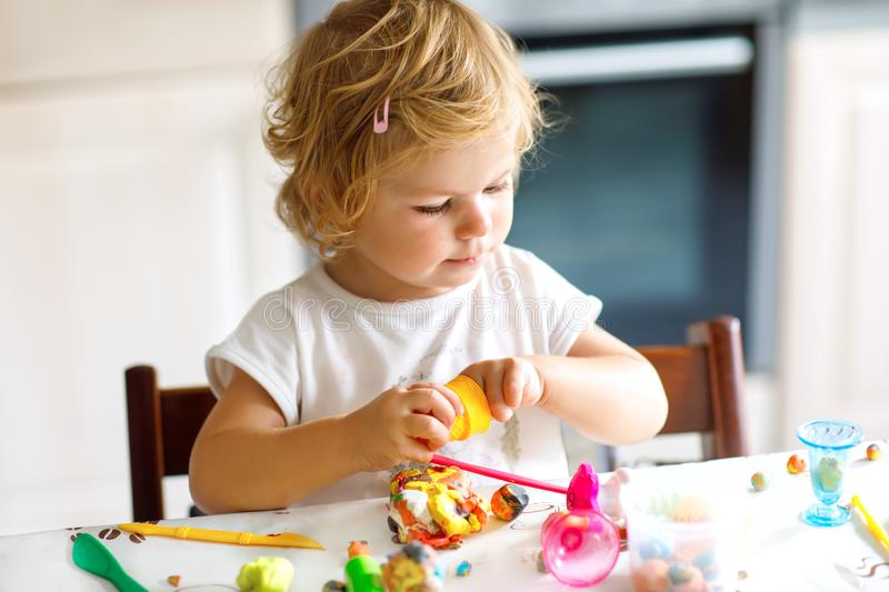 Adorable cute little toddler girl with colorful clay. Healthy baby playing and creating toys from play dough. Small kid royalty free stock photography
