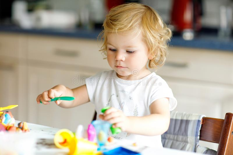 Adorable cute little toddler girl with colorful clay. Healthy baby playing and creating toys from play dough. Small kid stock images