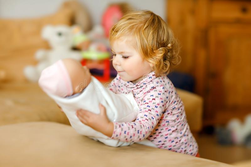 Adorable cute little toddler girl playing with doll. Happy healthy baby child having fun with role game, playing mother royalty free stock image