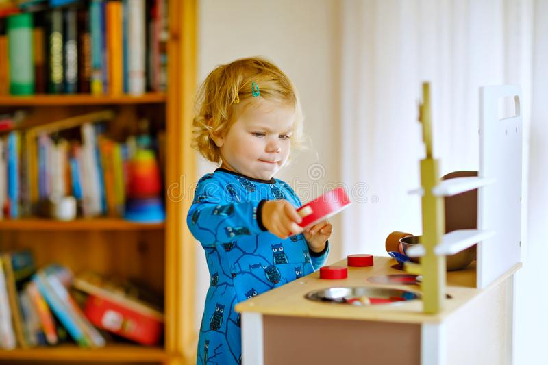 Adorable cute little toddler girl playing with toy kitchen Happy healthy baby child having fun with role game, playing royalty free stock photos