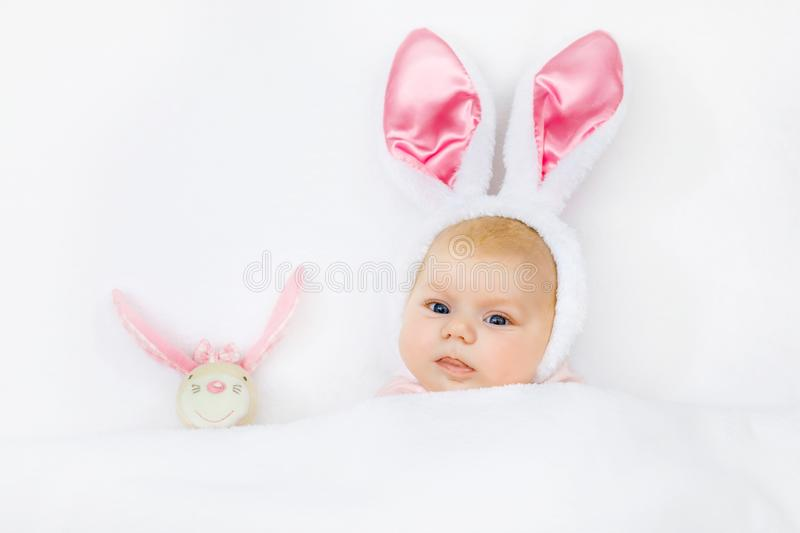 Adorable cute newborn baby girl in Easter bunny costume and ears. Lovely child playing with plush rabbit toy. Holiday royalty free stock photography