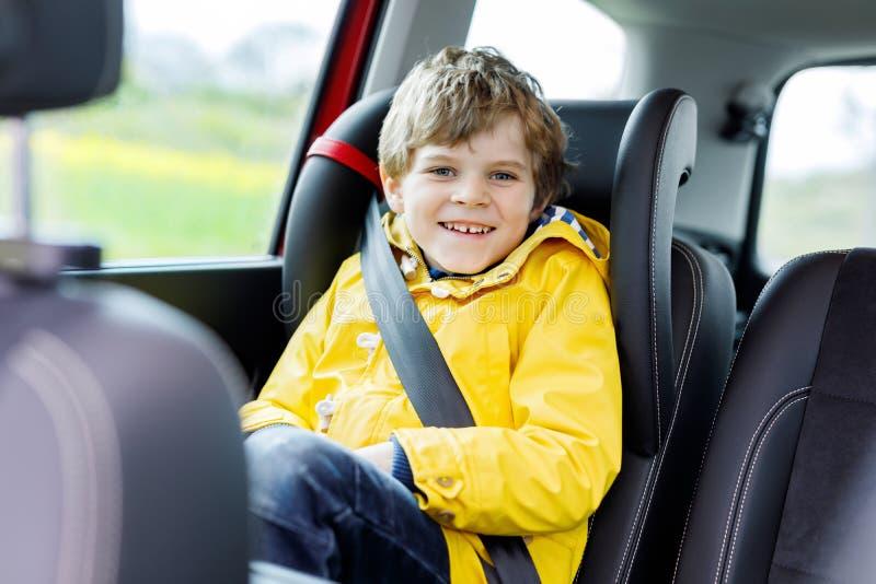 Adorable cute preschool kid boy sitting in car in yellow rain coat. Little school child in safety car seat with belt stock photo