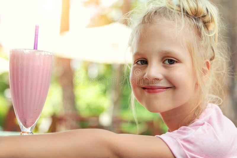 Adorable cute preschooler caucasian blond girl portrait sipping fresh tasty strawberry milkshake coctail at cafe outdoors. royalty free stock images