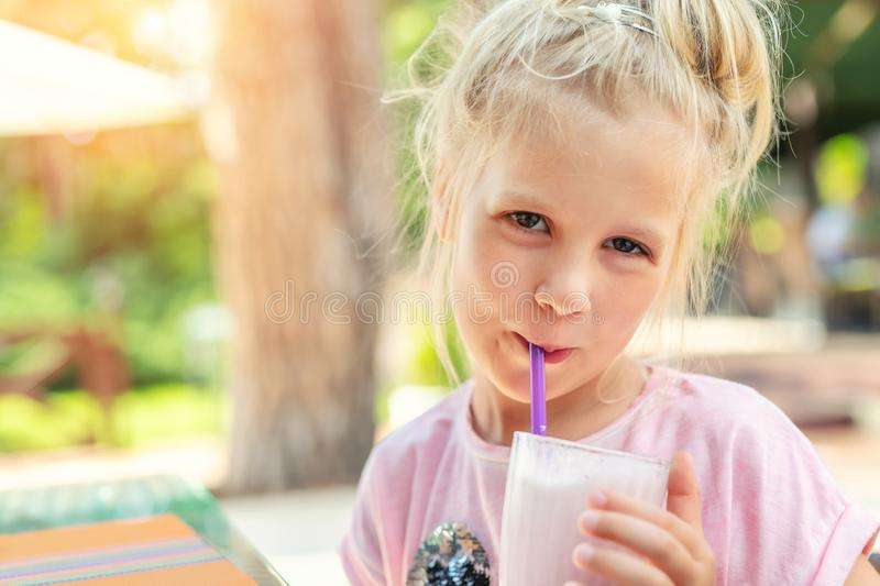 Adorable cute preschooler caucasian blond girl portrait sipping fresh tasty strawberry milkshake coctail at cafe outdoors. Children healthy diet and nutrtion stock photography