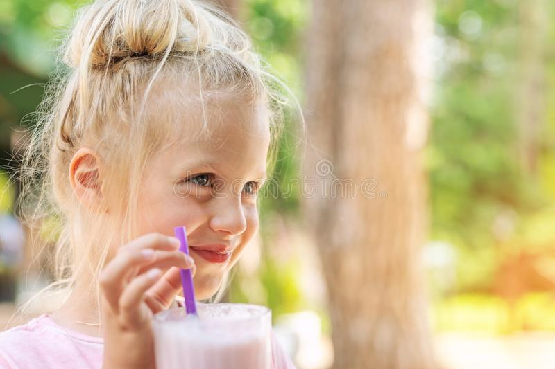 Adorable cute preschooler caucasian blond girl portrait sipping fresh tasty strawberry milkshake coctail at cafe outdoors. royalty free stock photo