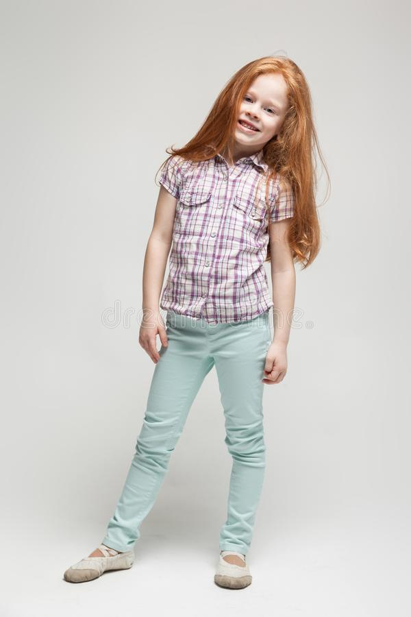 Adorable cute redhead little girl in plaid shirt, bright blue trousers and white boots stock photography