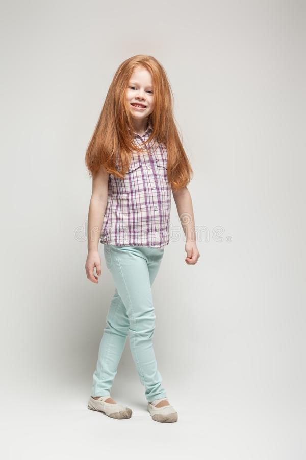 Adorable cute redhead little girl in plaid shirt, bright blue trousers and white boots royalty free stock images