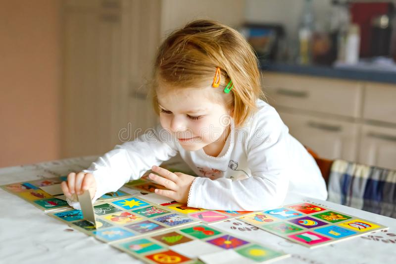 Adorable cute toddler girl playing picture card game at home or nursery. Happy healthy child training memory, thinking royalty free stock image