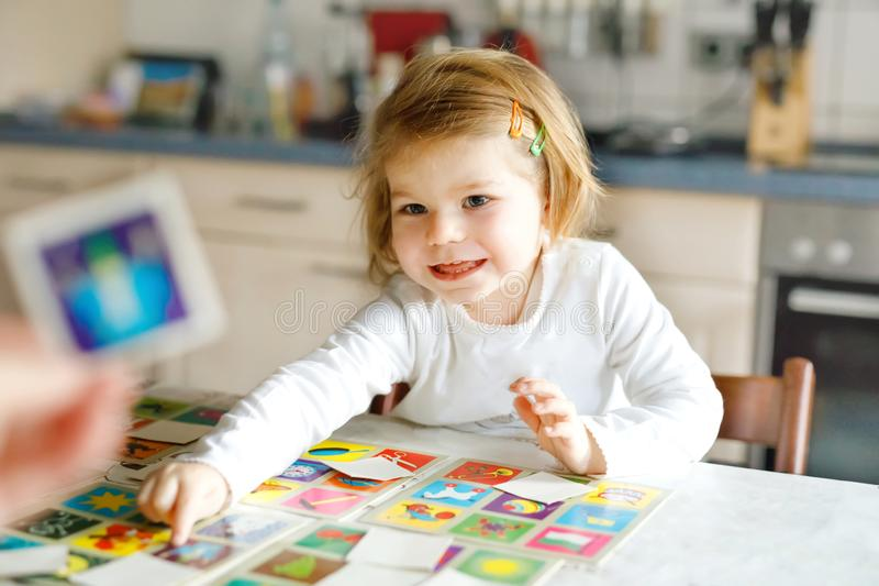Adorable cute toddler girl playing picture card game with mother or father. Happy healthy child training memory royalty free stock photos