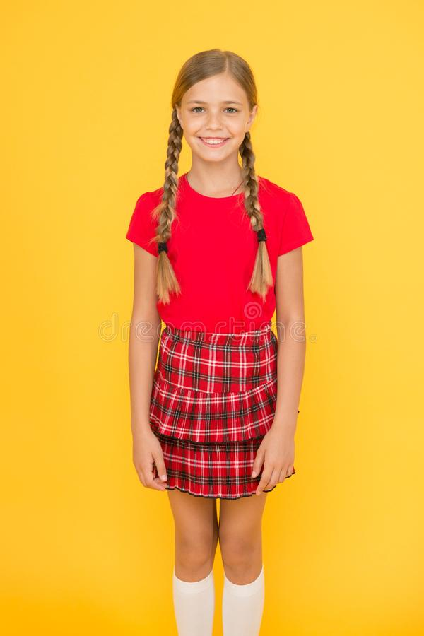 Adorable cutie. Cute little girl charming smile on yellow background. Happy small girl wearing red clothes. Girl with stock images