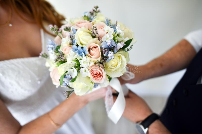 Adorable delicate wedding bouquet in yellow and blue colors in the hands of the bride.  royalty free stock photography