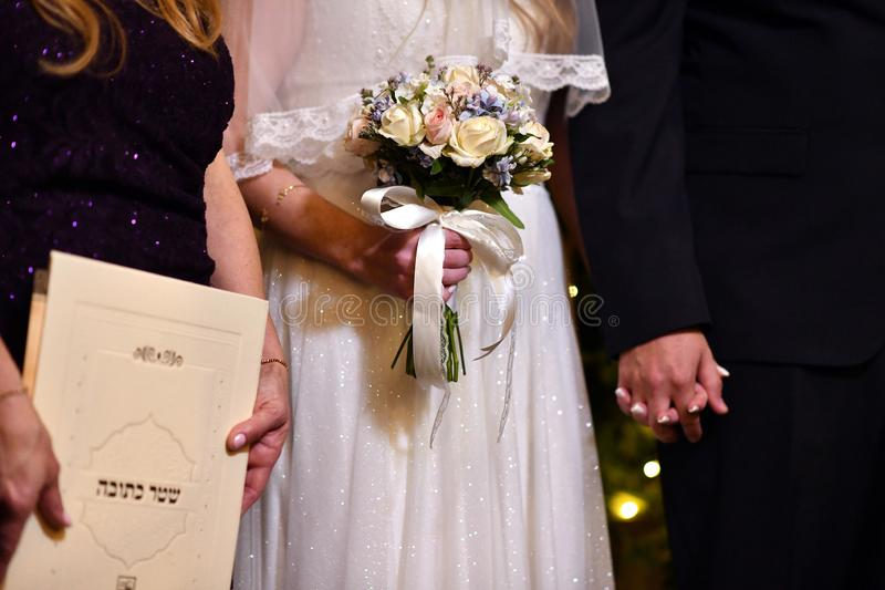 Adorable delicate wedding bouquet in yellow and blue colors in the hands of the bride. Written in hebrew - Ketubah certificate royalty free stock image