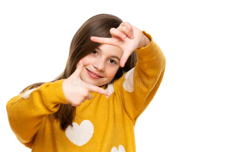 Adorable elementary age girl smiling while looking at camera and making photo frame hand gesture. Studio shot on white background. Adorable elementary age girl royalty free stock image