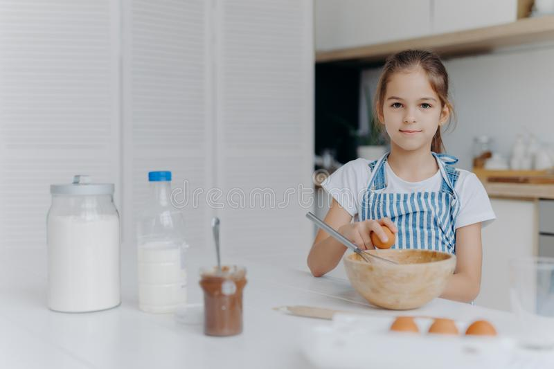 Adorable European child enjoys cooking activity, breaks egg in bowl, whisks ingredients, prepares tasty pastry, being young cook, royalty free stock photos