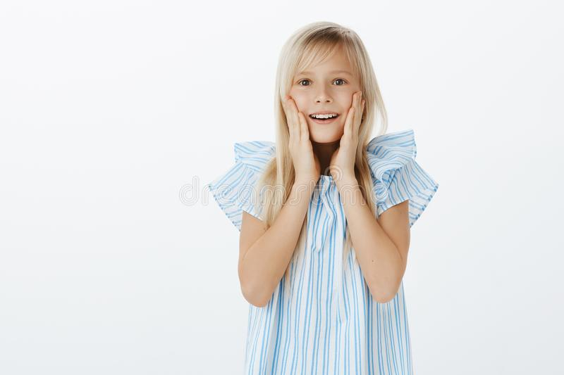 Adorable european young girl with blond hair in trendy blue blouse, gasping, holding hands near opened mouth, smiling royalty free stock photos