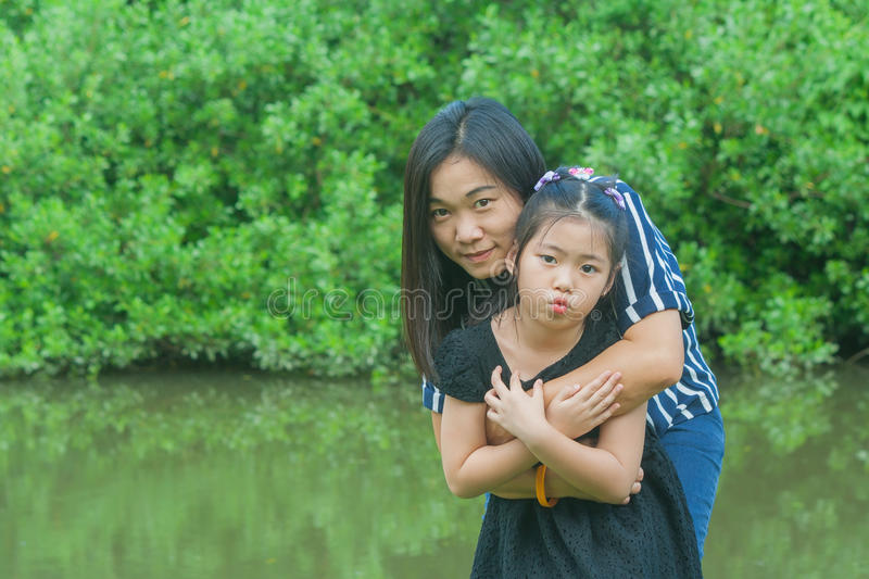 Adorable Family Concept : Asian woman and children standing on green grass, smiling and hug together. stock images