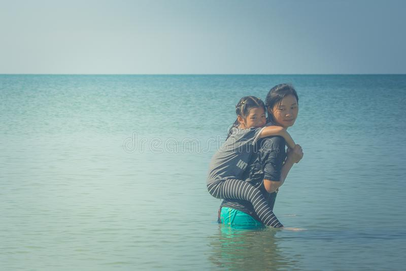 Cute little girl riding on woman back, They are standing in the sea and feeling happiness. royalty free stock image