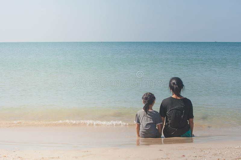 Woman and children sitting back to back on sand beach and looking to seascape. royalty free stock image