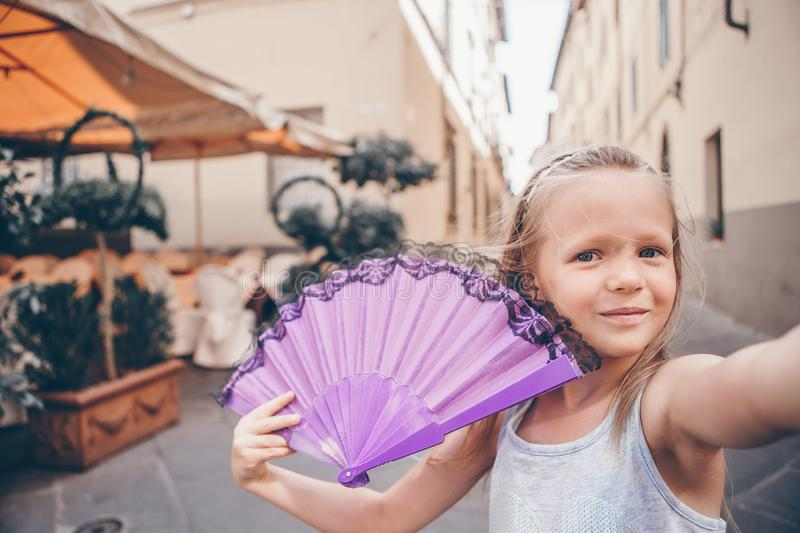 Adorable fashion little girl outdoors in European city. Adorable happy little girl taking selfie outdoors in european city. Portrait of caucasian kid enjoy stock images