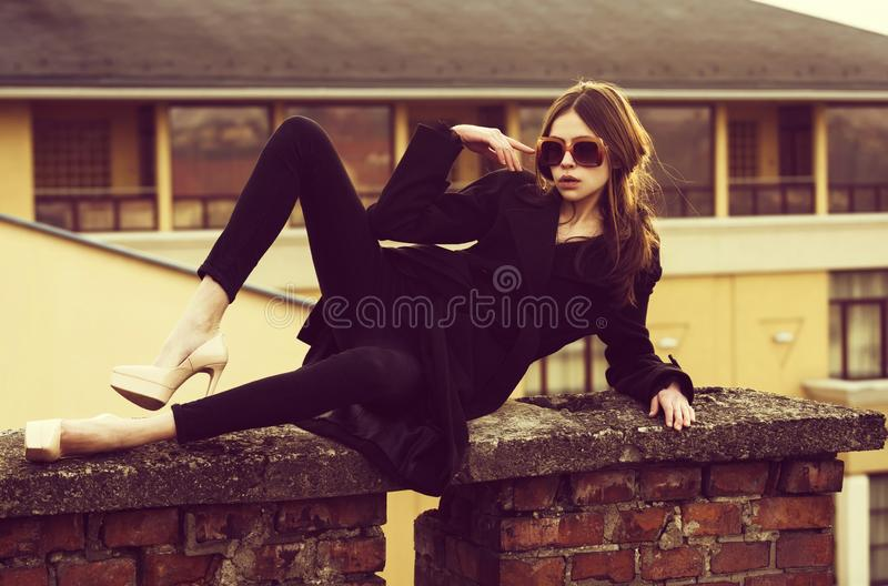 Adorable fashionable woman in vintage sunglasses lying on brick fence royalty free stock image