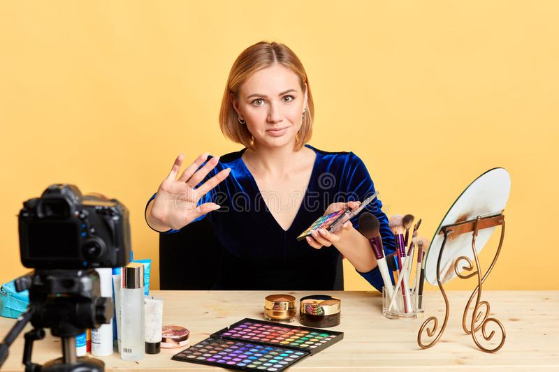 Adorable female beauty expert pulls hand towards camera, shows stop gesture. Adorable young female beauty expert pulls hand towards camera, shows stop gesture royalty free stock photography