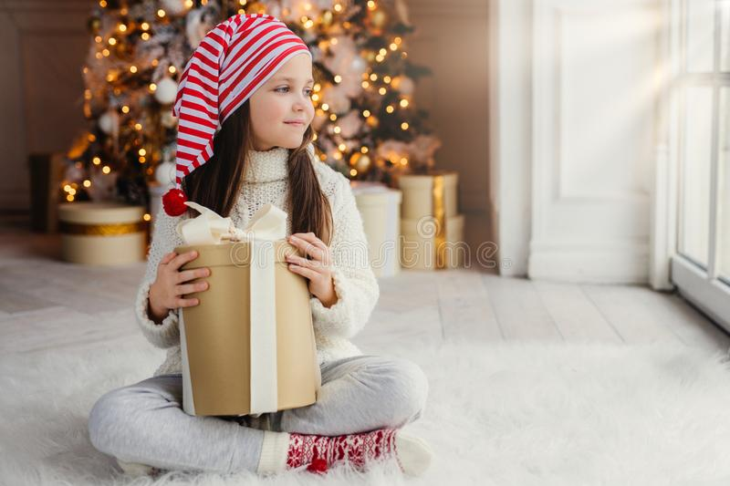 Adorable female child wears santa claus hat, warm clothes, hold wrapped gift box, sits against decorated New Year tree. Happy pret royalty free stock images