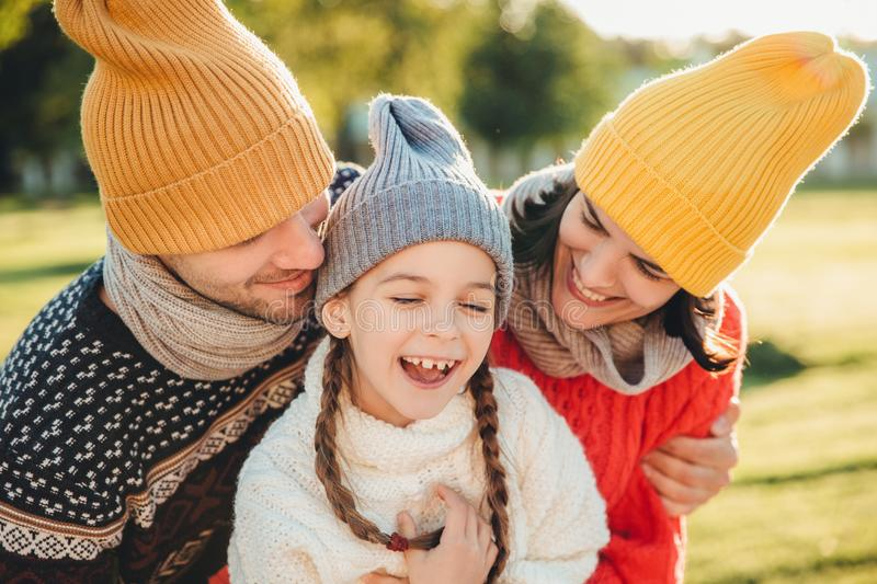 Adorable funny small kid has fun with parents who look at her with great love, enjoy spending free time together, admire beautiful royalty free stock image