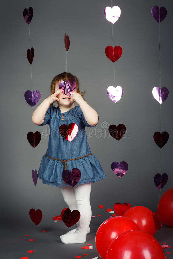 Adorable funny white Caucasian little girl toddler in studio with red balloons hearts on grey background making faces having fun royalty free stock photos
