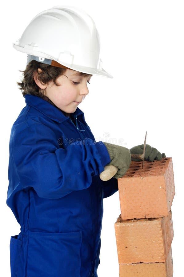 Adorable future builder constructing a brick wall stock image
