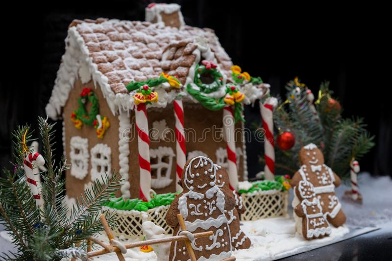 Adorable gingerbread family near snow-covered homemade gingerbread house with sprig of Christmas tree on dark background. Mockup for seasonal offers and stock image