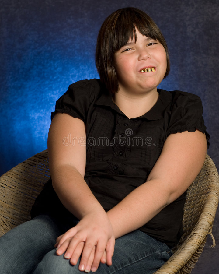 Adorable Girl. An adorable looking girl wearing some ugly rotten teeth, while getting her portrait done stock images