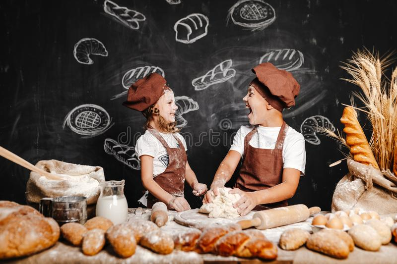 Adorable girl with brother cooking. Adorable girl with brother in aprons on table with bread loaves making fresh dough and having fun royalty free stock photos