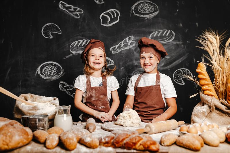 Adorable girl with brother cooking royalty free stock image