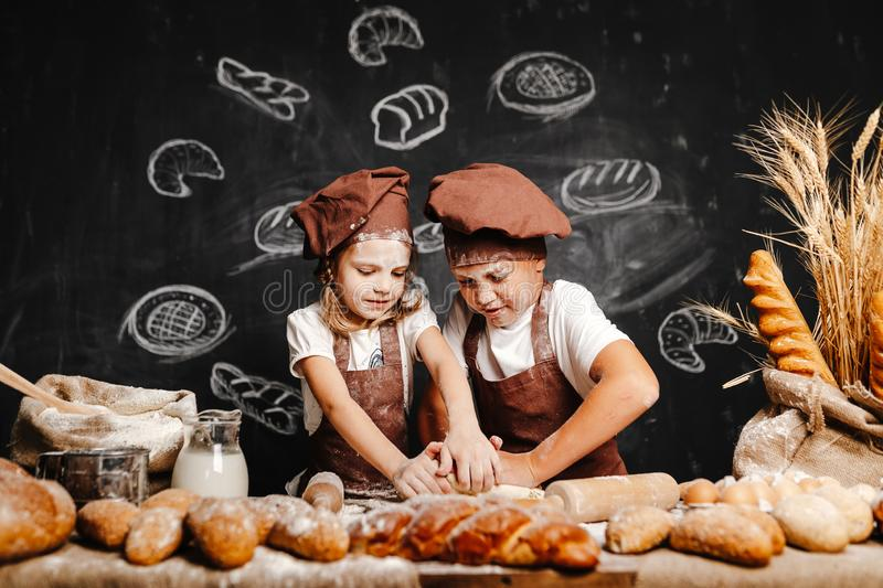 Adorable girl with brother cooking stock images