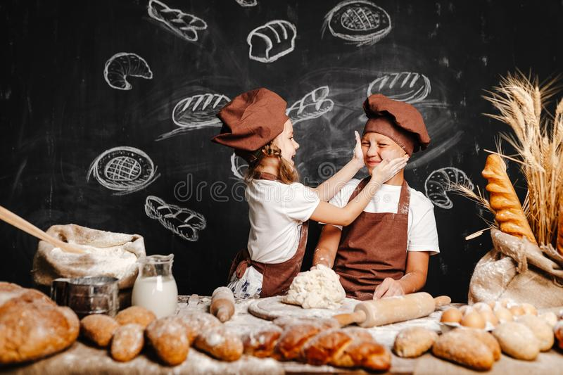 Adorable girl with brother cooking. Adorable girl with brother in aprons on table with bread loaves making fresh dough and having fun stock images
