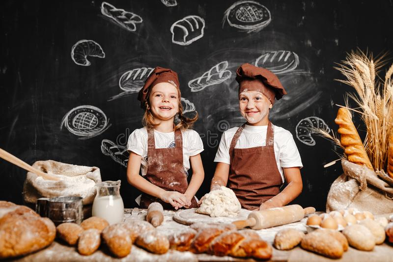 Adorable girl with brother cooking. Adorable girl with brother in aprons on table with bread loaves making fresh dough and having fun stock image