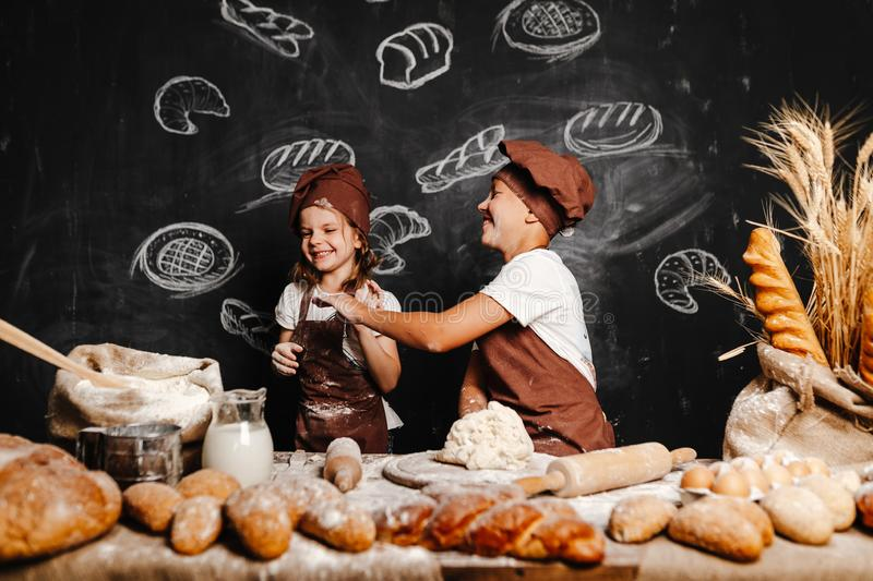 Adorable girl with brother cooking royalty free stock images