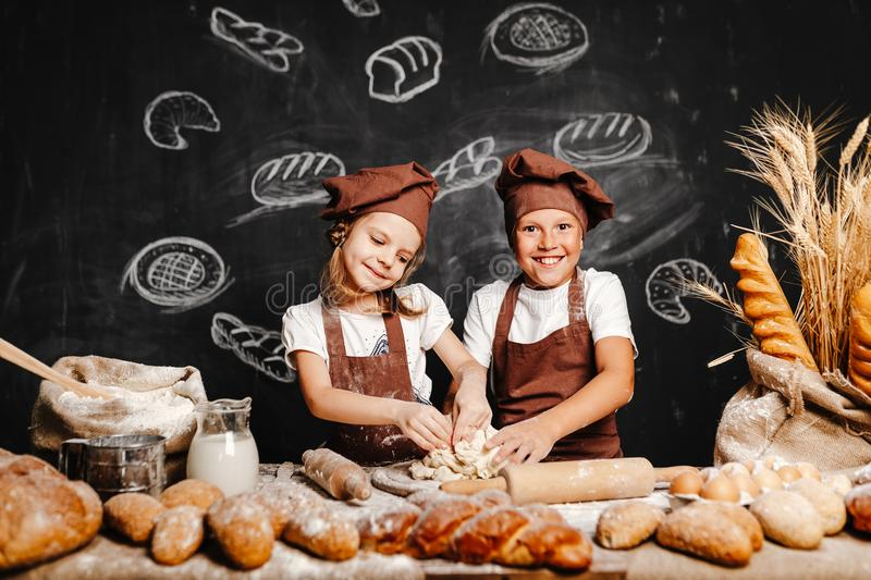 Adorable girl with brother cooking. Adorable girl with brother in aprons on table with bread loaves making fresh dough and having fun royalty free stock photography