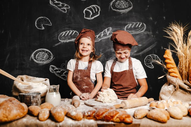 Adorable girl with brother cooking. Adorable girl with brother in aprons on table with bread loaves making fresh dough and having fun royalty free stock image