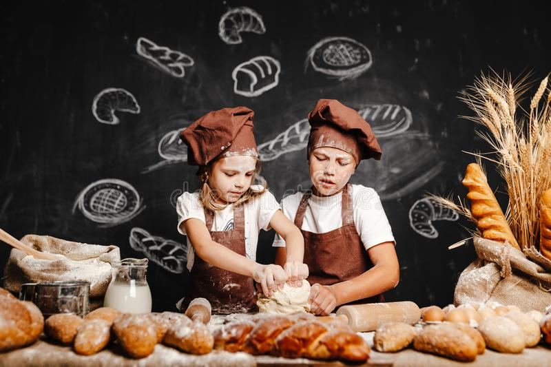 Adorable girl with brother cooking. Adorable girl with brother in aprons on table with bread loaves making fresh dough and having fun royalty free stock images