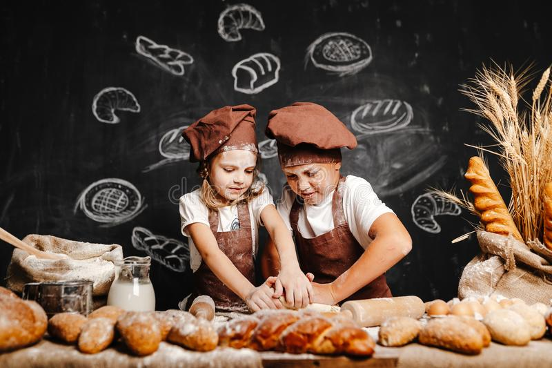 Adorable girl with brother cooking. Adorable girl with brother in aprons on table with bread loaves making fresh dough and having fun royalty free stock photo