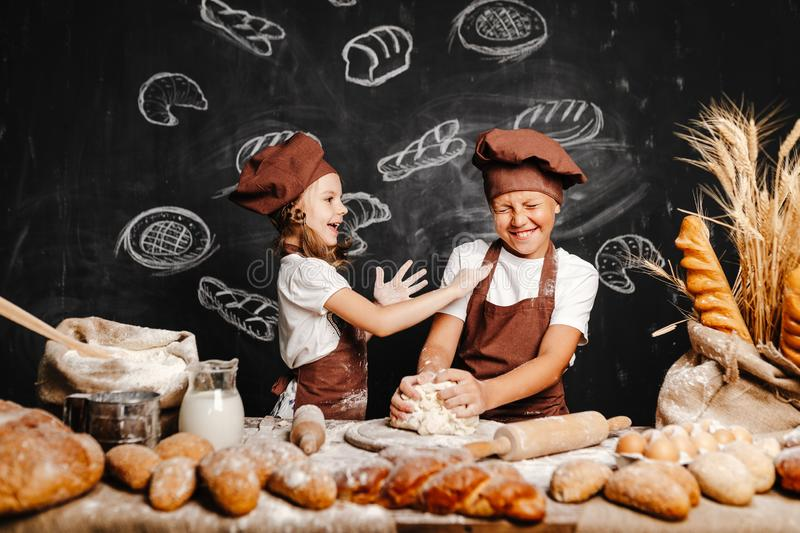Adorable girl with brother cooking royalty free stock photos