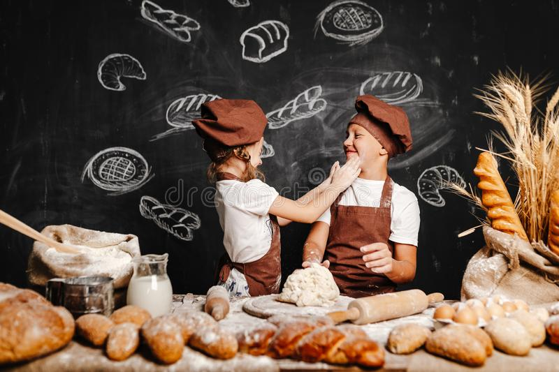 Adorable girl with brother cooking stock image