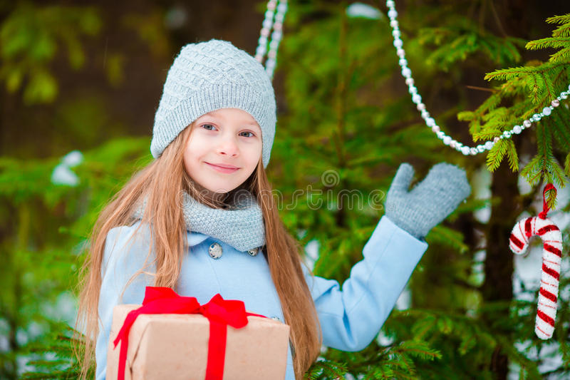 Adorable girl with christmas box gift in winter outdoors on Xmas eve. Cute little girl with christmas box gift in winter day royalty free stock photos