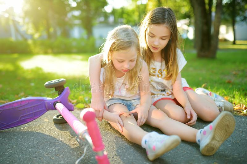 Adorable girl comforting her little sister after she fell off her scooter at summer park. Child getting hurt while riding a kick royalty free stock photography