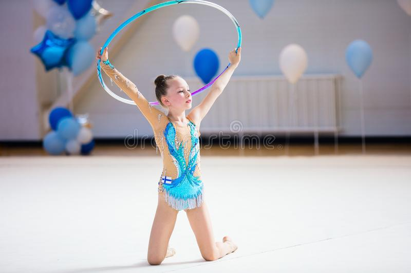 Adorable girl competing in rhythmic gymnastics. Adorable girl in rhythmic gymnastics competition with hoop royalty free stock image
