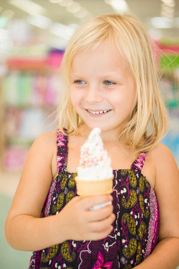 Adorable girl eat fruit ice cream in mall stock images