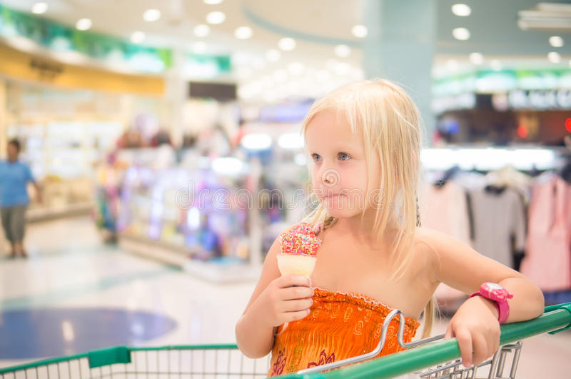 Adorable girl eat fruit ice cream with rainbow sprinkles in shop royalty free stock photo