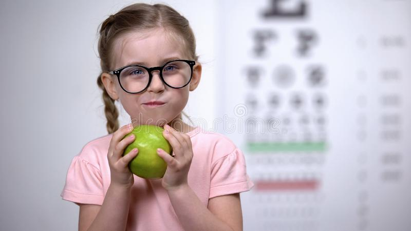 Adorable girl in glasses eating apple, natural vitamins for eyes, healthcare royalty free stock photos